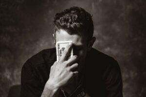 man holding money to head